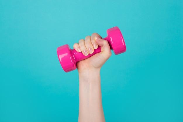 Разработка концепции. обрезанное фото спортивной женщины, держащей розовые гантели на синем бирюзовом фоне