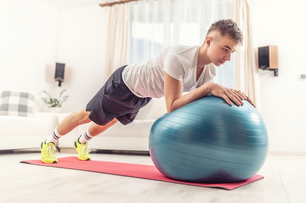 Working out at home by young man holding a plank position using a blue fit ball and red mat inside a living room.