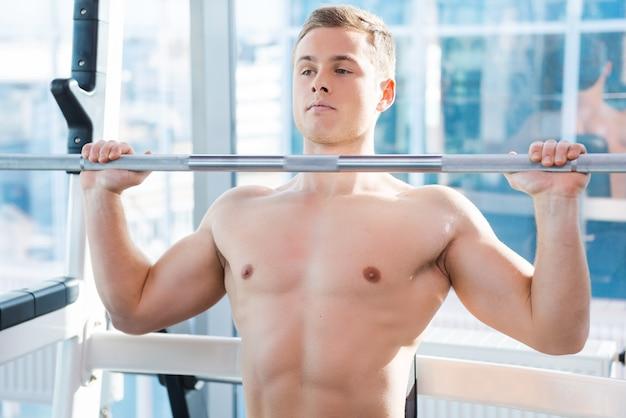 ベンチプレスでワークアウト。ベンチプレスで働いている集中した若い筋肉の男