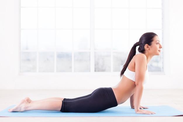Тренировка. вид сбоку красивой молодой индийской женщины, тренирующейся на коврике для йоги
