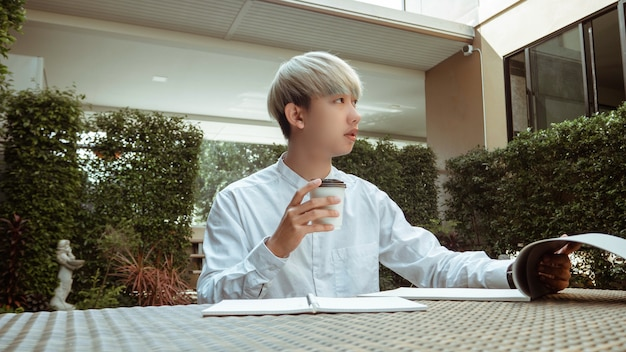 Working outdoor concept a cool young boy holding a cup of hot americano working peacefully in a co-working space of his condominium.