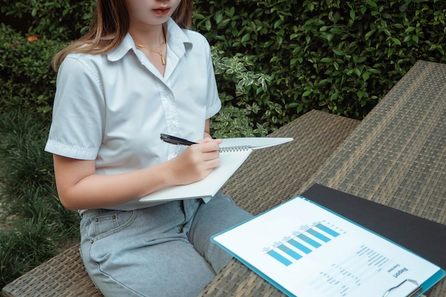 Working outdoor concept a female teenager sitting in a garden writing to summarize information from the graph.