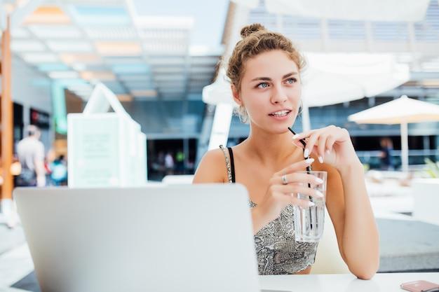 屋外での作業。ファンキーな帽子のラップトップに取り組んで、屋外に座っている間笑顔で美しい女性