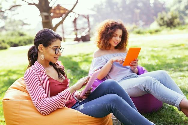 屋外での作業。椅子に座ってタブレットで作業している陽気な黒髪の女性