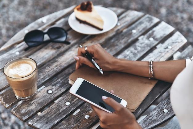 Работа на открытом воздухе. крупный план молодой женщины, использующей свой смартфон, сидя в ресторане на открытом воздухе