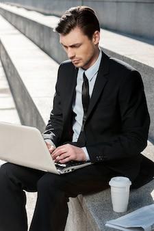 Работа на открытом воздухе. обрезанное изображение веселый бизнесмен с помощью ноутбука