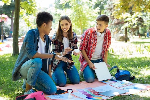 밖에서 일 해요. 외부 프로젝트 작업 과정을 즐기는 세 명의 빛나는 유망 미술 학생