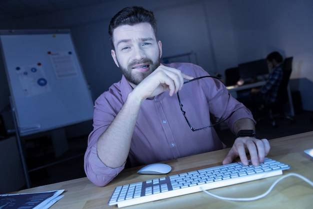 초과 근무. 잘 생긴 좋은 피곤 it 남자는 컴퓨터에 앉아있는 동안 그의 안경을 벗고 직장에서 쉬고