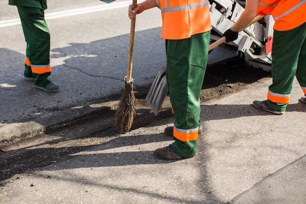 작업 포장재는 도로를 수리하기 전에 구멍에서 파편을 청소합니다.