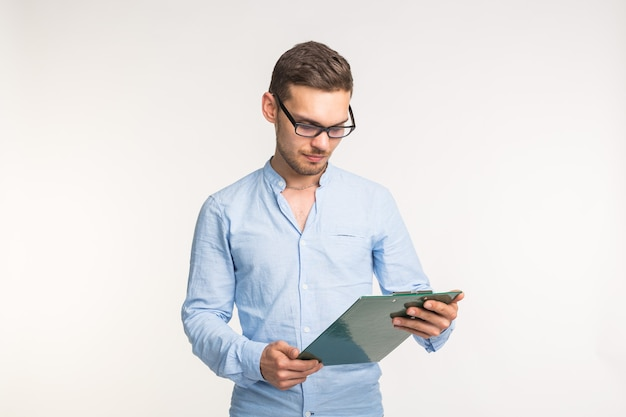Working and people concept - handsome young man in glasses watching on notes over the white wall.