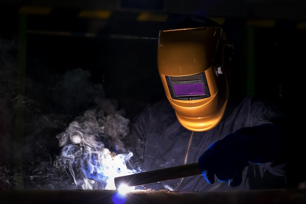 Working person about welder steel using electric welding machine.