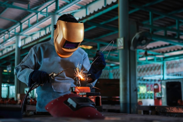 Working person about welder steel using electric welding machine