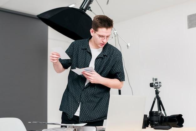 Working photographer man holding photographs