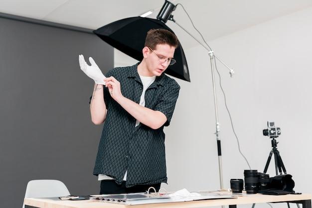 Рабочий фотограф человек ставит свои белые перчатки