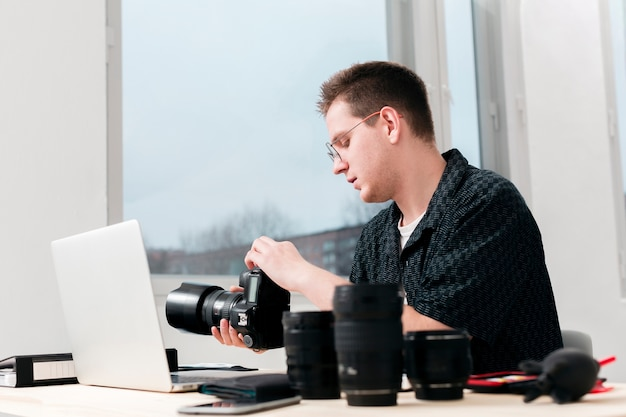 Working photographer man sitting at his desk