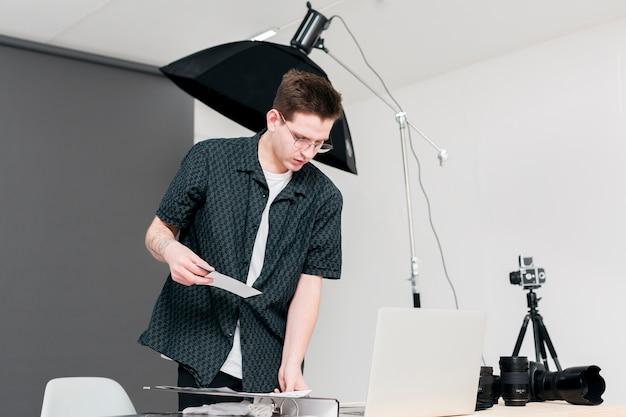 Working photographer man standing in his studio