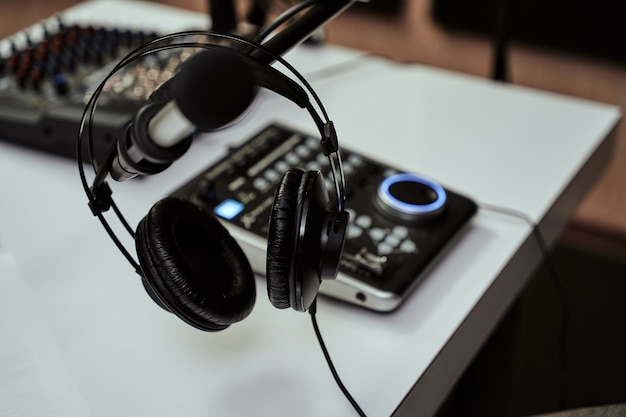 Working place of radio host close up of headphones microphone and sound mixing desk on the table in