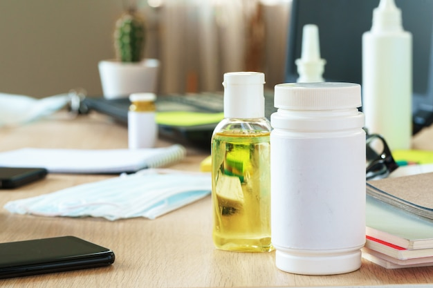 Working place table with small bottle of antibacterial sanitizer alcohol gel
