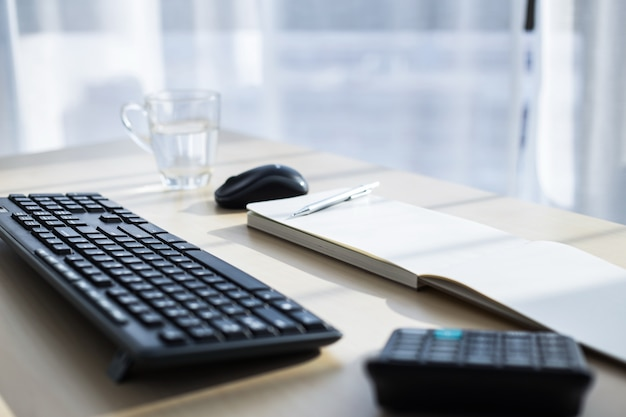 Рабочее место с клавиатурой, мышью, калькулятором и ручкой