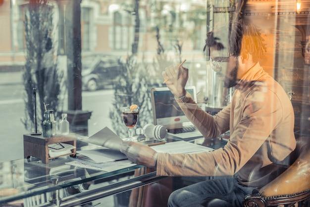 Рабочий процесс. внимательный бородатый мужчина склоняет голову при проверке документов на работу