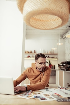 작업 과정. 그의 입에 연필로 노트북에 앉아 그의 새로운 모델의 사진을보고 창조적 인 패션 디자이너.