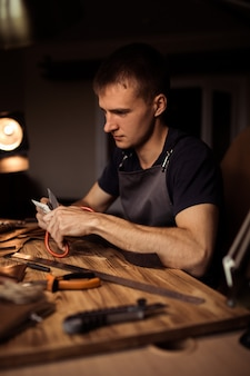 Working process of the leather belt in the leather workshop. man holding crafting tool and working. tanner in old tannery. wooden table background. close up man arm