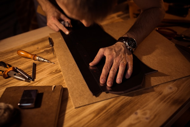 Working process of the leather belt in the leather workshop. man holding crafting tool and working. tanner in old tannery. wooden table background