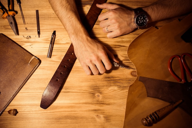 Working process of the leather belt in the leather workshop. man holding hands on wooden table. crafting tools on background. tanner in old tannery. close up men arm