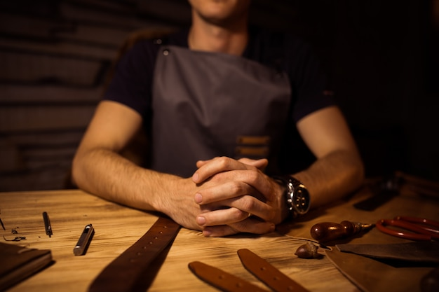 Working process of the leather belt in the leather workshop. man holding hands on wooden table. crafting tools on background. tanner in old tannery. close up men arm.