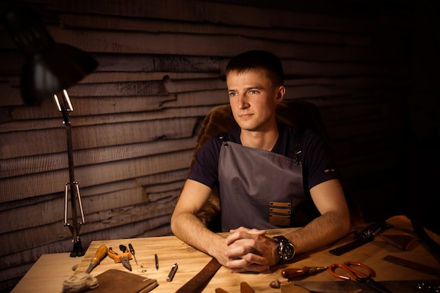 Working process of the leather belt in the leather workshop. man holding hands on wooden table. crafting tools on background. tanner in old tannery.