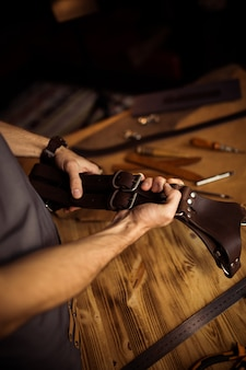 Working process of the leather belt in the leather workshop. man holding photographer's belt for camera. tool on wooden background. tanner in old tannery.