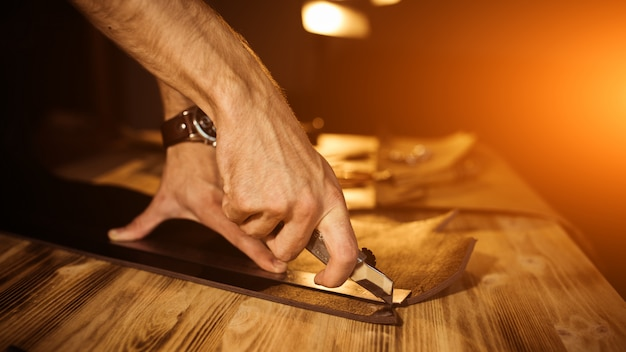 Working process of the leather belt in the leather workshop. man holding tool. tanner in old tannery. wooden table surface. close up man arm. warm light for text and design. web banner size