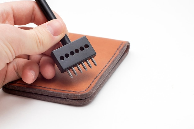 Working process of the leather wallet. man holding punching tool.