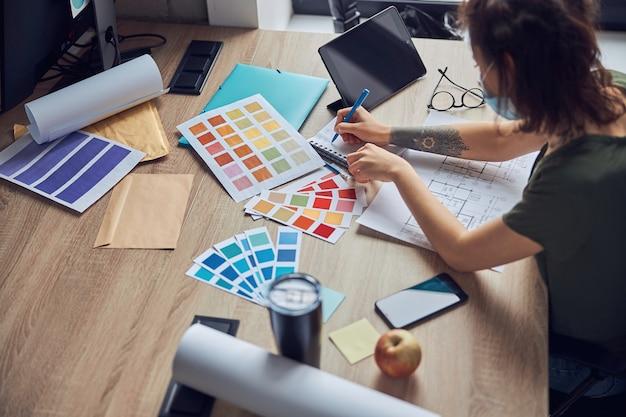 색상 샘플을 선택하는 노트북에 메모를 하는 여성 인테리어 디자이너의 작업 과정