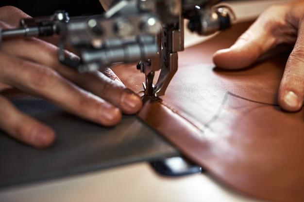 革職人の加工工程。タナーまたはスキナーは専用ミシンで革を縫い、クローズアップします。ミシンで作業者が縫います。