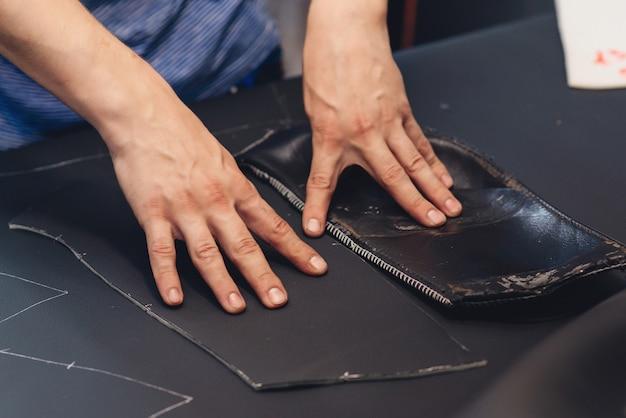 카시트 커버 봉제 작업 과정. 수제 가죽 장인. 작업자 바느질 가죽 제품입니다. 가죽공방. 공예 도구를 들고 작업하는 남자, 닫습니다. 손으로 물건 만들기.