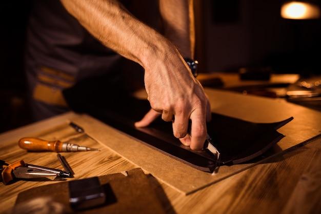 가죽 작업장에서 가죽 벨트의 작업 과정. 공예 도구를 들고 작업하는 남자. 오래된 무두질 공장. 나무 테이블 배경입니다.
