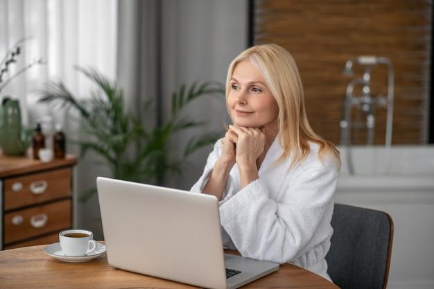 Рабочий процесс. довольно блондинка женщина сидит за ноутбуком и смотрит вдумчиво
