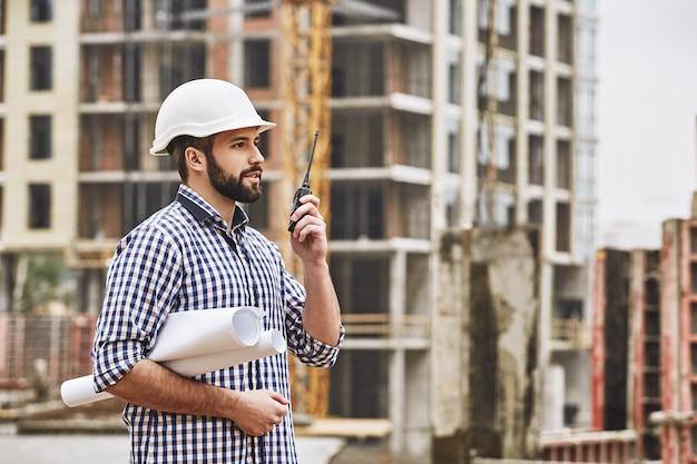 と話している白い保護ヘルメットの建設ビルダーで若い作業プロセスの専門家