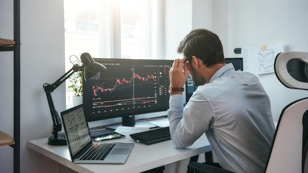 여러 컴퓨터 화면의 차트를 보고 데이터를 분석하는 작업 프로세스 스마트 남성 상인