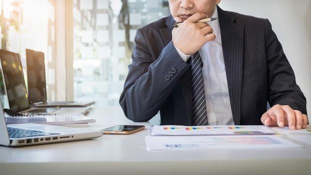 作業プロセスの起動。新しい金融プロジェクトで木製テーブルで働くビジネスマン。テーブル上の現代的なノートブック。手をつなぐペン