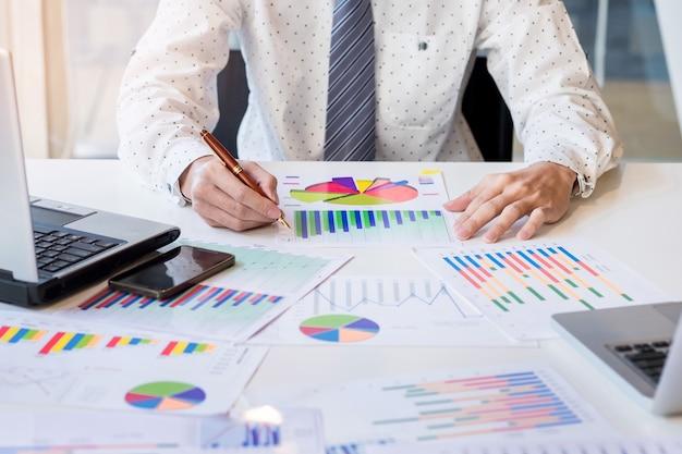 작업 프로세스 시작 새로운 금융 프로젝트와 나무 테이블에서 일하는 사업가. 테이블에 현대 노트북입니다. 펜 잡고 손