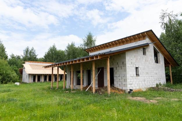 作業プロセス、ケイ酸塩およびガスケイ酸塩ブロックと木材からの郊外建設。屋根のある平屋のフレーム。