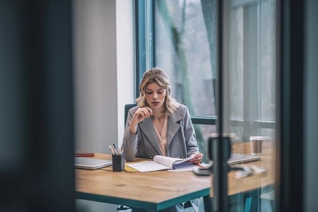 作業工程。オフィスの窓に戻ってテーブルでドキュメントを操作することを考えているスーツの若い大人のビジネス女性