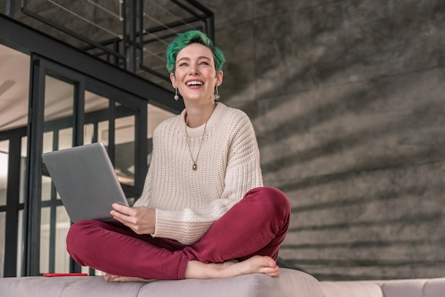 リモートで作業しています。ベージュのセーターを着た緑の目の女性と、リモートで働く素敵なアクセサリー