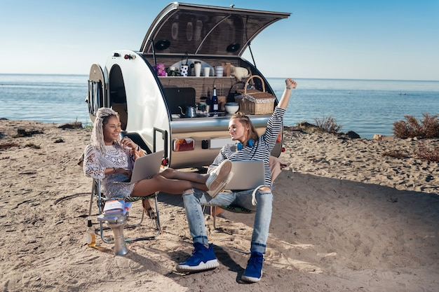 원격으로 작업합니다. 모바일 홈에 살고있는 사랑하는 현대 부부가 원격으로 의자에 앉아 작업