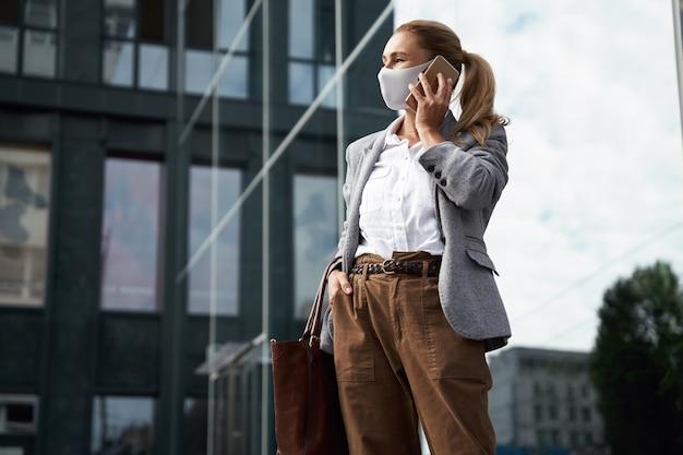 コロナウイルスの自信を持ってビジネスウーマンが話している保護フェイスマスクを身に着けている間に安全に働く
