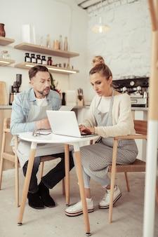 並んで作業します。カフェの厨房機器の前に座って仕事をしている2人の焦点を絞ったビジネスパートナー。