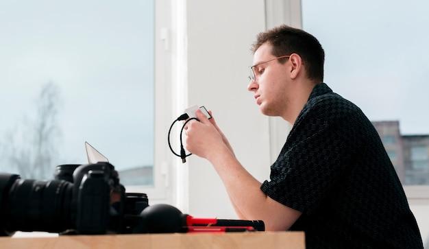 Lavoro laterale fotografo uomo e macchine fotografiche