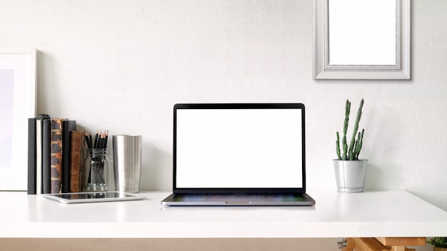 Working space and copy space. mockup poster and blank screen laptop on white desk